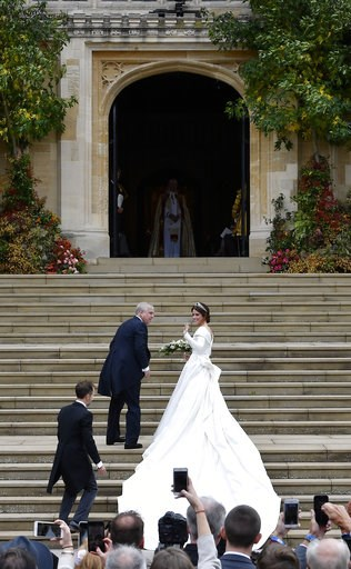 (Toby Melville, Pool via AP). Britain's Princess Eugenie, accompanied by her father Prince Andrew, arrives for her wedding ceremony to Jack Brooksbank in St George's Chapel, Windsor Castle, near London, England, Friday Oct. 12, 2018.