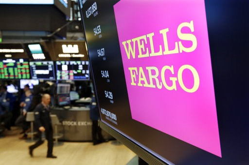 (AP Photo/Richard Drew, File). FILE- In this May 17, 2018, file photo the logo for Wells Fargo appears above a trading post on the floor of the New York Stock Exchange. Wells Fargo reports earnings Friday, Oct. 12, 2018.