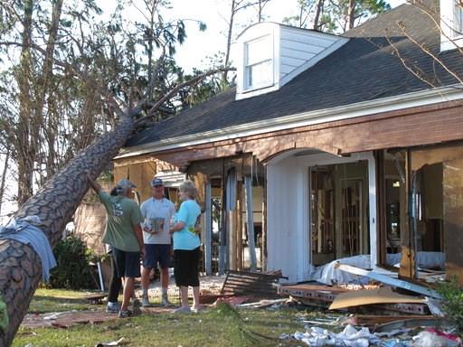 (AP Photo/Russ Bynum). Rex Buzzett, far left, his son Josh Buzzett and neighbor Hilda Duren stand outside the Buzzett's home, Thursday, Oct. 11, 2018, that was gutted by a storm surge in Port St. Joe, Fla. Hurricane Michael devastated several homes ove...