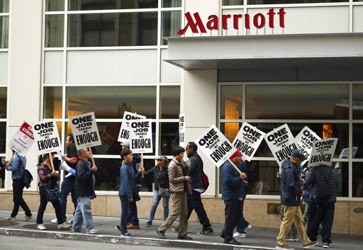 (AP Photo/Ben Margot, File). FILE - In this Oct. 4, 2018 file photo, hotel workers strike in front of a Marriott hotel in San Francisco. New technology threatening to make some hotel jobs obsolete is among the concerns prompting thousands of Marriott w...