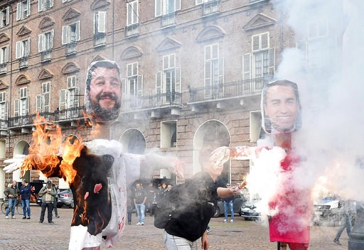 (Alessandro Di Marco/ANSA via AP). Protesters burn lookalike dummies of Italian deputy premiers Matteo Salvini, left, and Luigi Di Maio, during a students protest, in Turin, Italy, Friday, Oct.12, 2018. Italian students across the country demonstrated ...