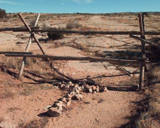 (AP Photo/Ed Andrieski, File). FILE - In this Oct. 9, 1999 file photo, a cross made of stones rests below the fence in Laramie, Wyo. where a year earlier, University of Wyoming student Matthew Shepard was tied and pistol whipped into a coma. He later d...