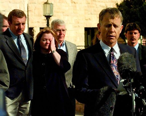 (AP Photo/Ed Andrieski, File). FILE - In this Nov. 4, 1999 file photo, Judy Shepard, left, wipes tears from her eyes with Detective Sgt. Rob DeBree at her side, as her husband Dennis reads a statement to the media regarding Aaron McKinney's plea bargai...