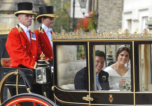 (AP Photo/Rui Vieira). Princess Eugenie of York, right, and Jack Brooksbank smile as they travel from St George's Chapel to Windsor Castle after their wedding at St George's Chapel, Windsor Castle, near London, England, Friday, Oct 12, 2018.