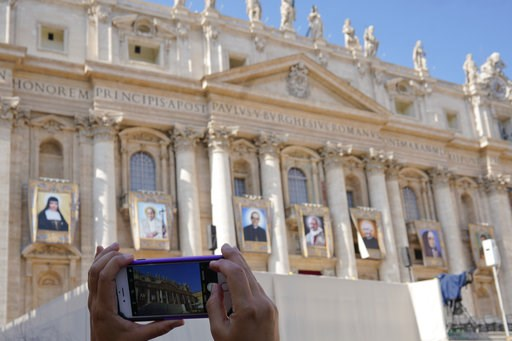 (AP Photo/Andrew Medichini). A woman takes photos of tapestries of Roman Catholic Archbishop Oscar Romero, 3rd from left, and Pope Paul VI, 4th from left, hanging from a balcony of the facade of St. Peter's Basilica at the Vatican, Saturday, Oct. 13, 2...