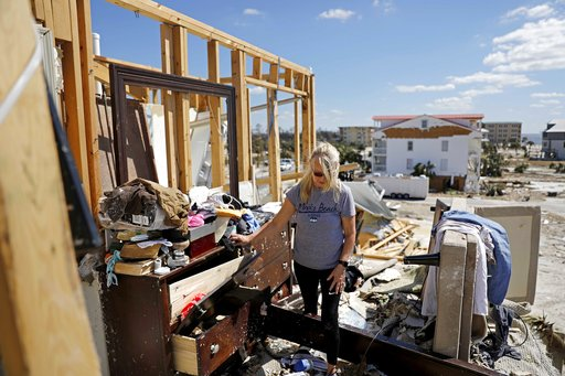 "(AP Photo/David Goldman). Candace Phillips sifts through what was her third-floor bedroom while returning to her damaged home in Mexico Beach, Fla., Sunday, Oct. 14, 2018, in the aftermath of Hurricane Michael. ""We spent 25 years of our marriage workin..."