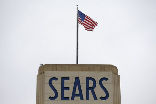 (AP Photo/Seth Wenig). An American flag flies above a Sears department store sign in Hackensack, N.J., Monday, Oct. 15, 2018. Sears filed for Chapter 11 bankruptcy protection Monday, buckling under its massive debt load and staggering losses.
