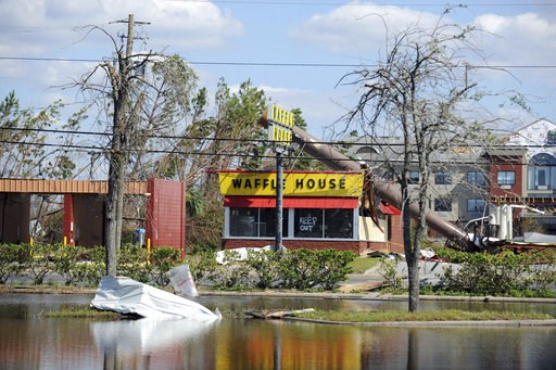 (Carlos R. Munoz/Sarasota Herald-Tribune via AP). In this Sunday, Oct. 14, 2018, photo, a billboard lies atop a Waffle House restaurant after being knocked down by Hurricane Michael, in Panama City, Fla.