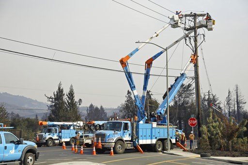(AP Photo/Eric Risberg, File). FILE - In this Oct. 11, 2017 file photo, a Pacific Gas & Electric crew works at restoring power along the Old Redwood Highway in Santa Rosa, Calif. Northern California's biggest utility has taken the unprecedented ste...