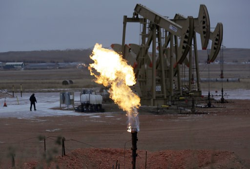(AP photo/Eric Gay, File). FILE - In this Oct. 22, 2015, file photo, workers tend to oil pump jacks behind a natural gas flare near Watford City, N.D. Since Donald Trump took office, America's exports of liquid natural gas and crude oil have surged, ri...