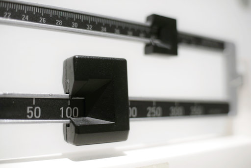 (AP Photo/Patrick Sison, File). FILE - This April 3, 2018 file photo shows a closeup of a beam scale in New York. New research, published Tuesday, Oct. 16 in the Journal of the American Medical Association, suggests obesity surgery may dramatically low...