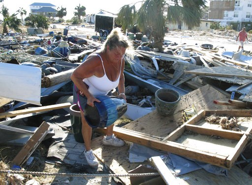 (AP Photo/Russ Bynum). In this Oct. 14, 2018 photo Dena Frost salvages an unbroken clay pot from the wreckage of her pottery business in Mexico Beach, Fla. For decades, the town has persisted as a stubbornly middlebrow enclave on what residents proudly...