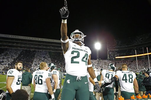 (AP Photo/Chris Knight). Michigan State's Elijah Collins (24) stands on the bench and celebrates after his team scored against Penn State with 19 seconds left in an NCAA college football game in State College, Pa., Saturday, Oct. 13, 2018.