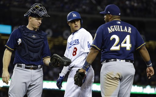 (AP Photo/Matt Slocum). Milwaukee Brewers' Jesus Aguilar and Los Angeles Dodgers' Manny Machado have words during the 10th inning of Game 4 of the National League Championship Series baseball game Tuesday, Oct. 16, 2018, in Los Angeles.