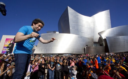 (AP Photo/Damian Dovarganes, File). FILE - In this Sept. 30, 2018, file photo, Phil Music & Artistic Director Gustavo Dudamel conducts musicians from the LA Phil, Youth Orchestra Los Angeles (YOLA) at the Celebrate LA: LA Phil 100 x CicLAvia event ...