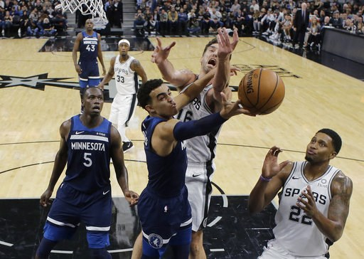 (AP Photo/Eric Gay). Minnesota Timberwolves guard Tyus Jones (1) tires to score past San Antonio Spurs center Pau Gasol (16) and forward Rudy Gay, right, during the first half of an NBA basketball game, Wednesday, Oct. 17, 2018, in San Antonio.