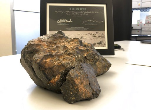 (AP Photo/Rodrique Ngowi). FILE - In this undated file photo, a 12-pound (5.5 kilogram) lunar meteorite discovered in Northwest Africa in 2017 rests on a table, in Amherst, N.H.  The lunar meteorite has been sold at auction for more than $600,000.Bosto...