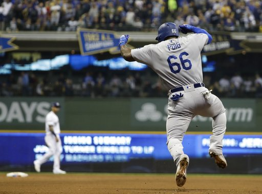 (AP Photo/Matt Slocum). Los Angeles Dodgers' Yasiel Puig reacts after hitting a three-run home run during the sixth inning of Game 7 of the National League Championship Series baseball game against the Milwaukee Brewers Saturday, Oct. 20, 2018, in Milw...