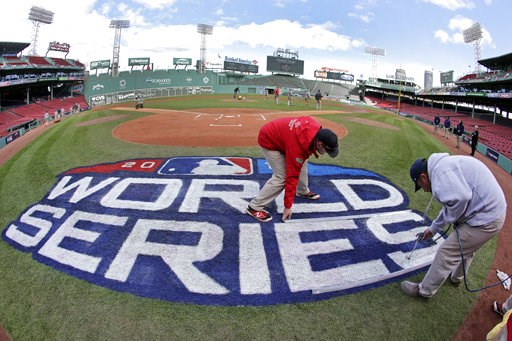 (AP Photo/Elise Amendola). Grounds crew members paint the World Series logo behind home plate at Fenway Park, Sunday, Oct. 21, 2018, in Boston as they prepare for Game 1 of the baseball World Series between the Boston Red Sox and the Los Angeles Dodger...