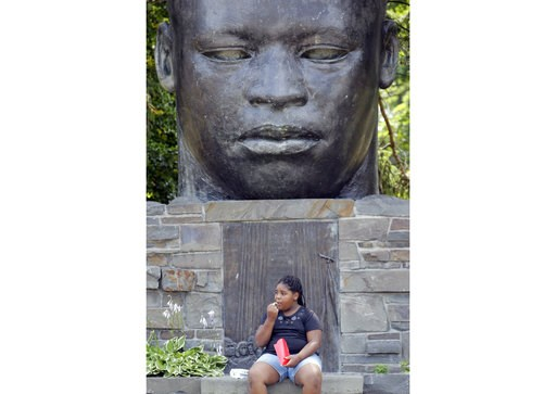 (AP Photo/David Duprey, File). FILE - In this July 13, 2012 file photo, Tonae Johnson eats her lunch in the park in front of a Martin Luther King Jr. statue during the warm summer weather in Buffalo, N.Y. A community activist says he has gathered more ...