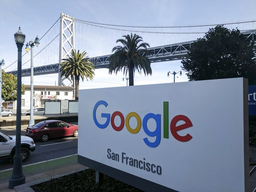 (AP Photo/Michael Liedtke). This photo shows signage outside the offices of Google in San Francisco with the San Francisco-Oakland Bay Bridge in the background, Wednesday, Oct. 31, 2018. Hundreds of Google employees are expected to temporality leave th...