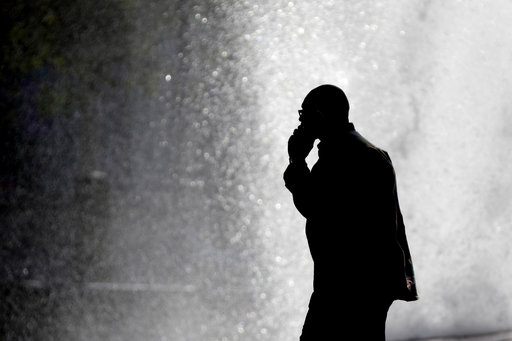 (AP Photo/Matt Rourke). FILE - In this Thursday, Oct. 11, 2012 file photo, a pedestrian talking on a cellphone is silhouetted in front of a fountain in Philadelphia. Two U.S. government agencies are giving conflicting interpretations of a safety study ...