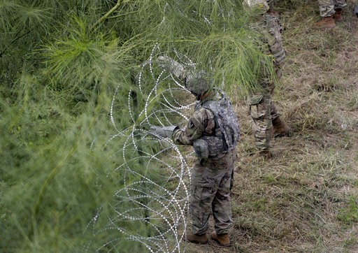 (AP Photo/Eric Gay). Members of the U.S.military place razor wire along the U.S.-Mexico border near the McAllen-Hidalgo International Bridge, Friday, Nov. 2, 2018, in McAllen, Texas.
