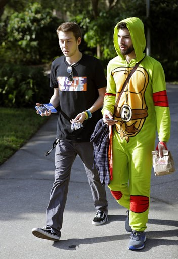 (AP Photo/John Raoux). In this Wednesday, Oct. 31, 2018 photo, Bradley Thornton, left, a student volunteer, escorts Gabriel Sanchez to a polling place on campus during a Vote for Our Lives event at the University of Central Florida in Orlando, Fla. Nin...