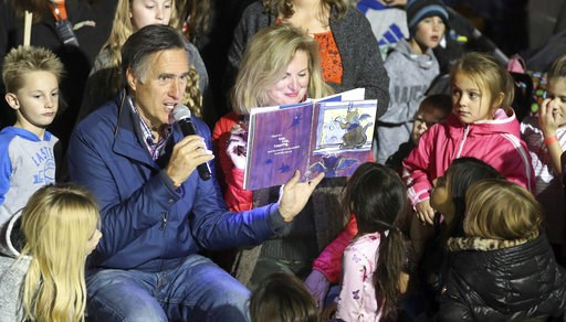 (AP Photo/Rick Bowmer). In this Friday, Nov. 2, 2018 photo, former GOP presidential nominee Mitt Romney and his wife Ann read a children's book during scary tales and smores bonfire at Cornbelly's Corn Maze & Pumpkin Fest at Thanksgiving Point in L...