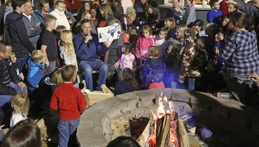 (AP Photo/Rick Bowmer). In this Friday, Nov. 2, 2018 photo, former GOP presidential nominee Mitt Romney reads during scary tales and smore bonfire at Cornbelly's Cornbelly's Corn Maze & Pumpkin Fest at Thanksgiving Point in Lehi, Utah. Romney is st...