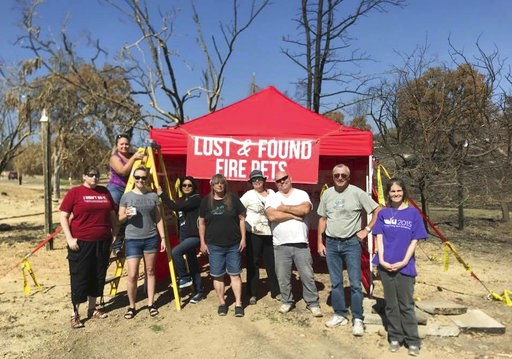 """(Courtesy of Stacey Jimenez via AP). In this undated photo, Volunteers with Carr Fire Pet Rescue and Reunification pose with their """"Lost and Found Fire Pets"""" kiosk in Redding, Calif. Volunteers continue to track and catch missing pets nearly two months..."""