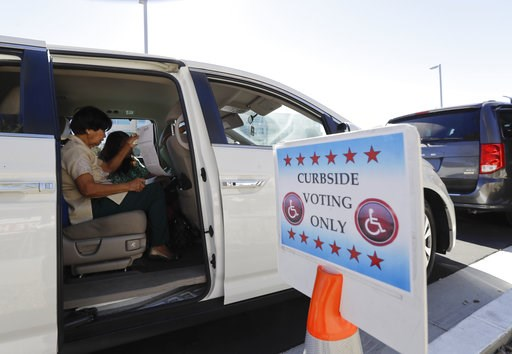 (AP Photo/Gregory Bull). Felicita Subhita, left, reviews her ballot as she uses curbside voting services during early voting Friday, Nov. 2, 2018, in San Diego.