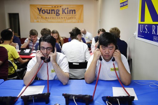 (AP Photo/Jae C. Hong). Charles Cannizzaro, left, and Ethan Cho, volunteers working for Young Kim, a candidate running for a U.S. House seat in the 39th District in California, call potential voters Saturday, Nov. 3, 2018, in Rowland Heights, Calif. Th...