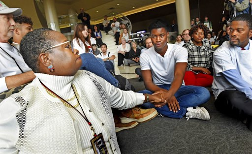 (Jean Pieri/Pioneer Press via AP). In this Oct. 25, 2018, photo Aura Wharton-Beck, left, an assistant professor in the School of Education at the University of St. Thomas and a graduate of the school, clasps hands with Kevyn Perkins, center, during a m...