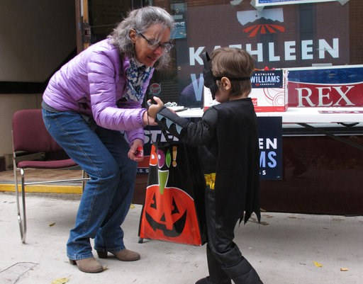 (AP Photo/Matt Volz). Democratic U.S. House candidate Kathleen Williams of Montana hands out Halloween candy to a child on Wednesday, Oct. 31, 2018, in Helena, Mont. Williams is trying to defeat Republican Rep. Greg Gianforte in Tuesday's election.