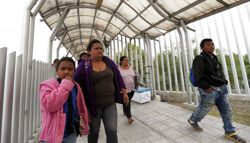 (AP Photo/Eric Gay, File). FILE- In this Saturday, Nov. 3, 2018, file photo immigrants seeking asylum in the United States walk off of the the International Bridge in Reynosa, Mexico. Asylum seekers already camping at border crossings worry that how th...