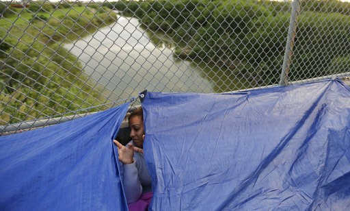 (AP Photo/Eric Gay, File). FILE- In this Friday, Nov. 2, 2018, file photo Maidelen Gonzales, an immigrant from Honduras seeking asylum in the United States, waits under a tarp on the Brownsville and Matamoros International Bridge in Matamoros, Mexico. ...