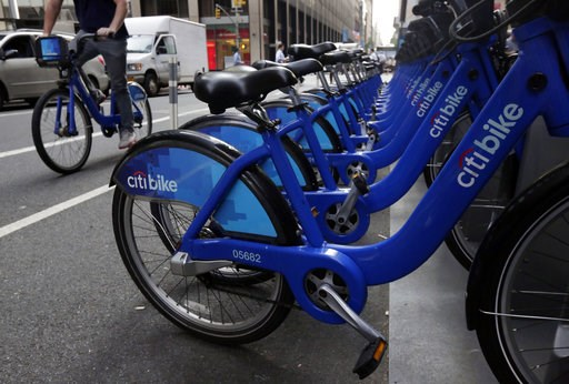 (AP Photo/Richard Drew, File). FILE- In this July 22, 2014, file photo parked Citi Bikes line a street in New York. Ride-share companies are capitalizing on voter enthusiasm ahead of Tuesday's midterm elections by offering free or discounted rides to t...