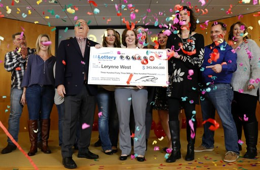 (AP Photo/Charlie Neibergall). Iowa Lottery CEO Terry Rich, left, presents a check to Lerynne West, of Redfield, Iowa, center, for her share of a nearly $700 million Powerball prize, Monday, Nov. 5, 2018, at the Iowa Lottery headquarters in Clive, Iowa...