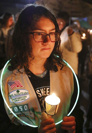 (Steve Kinderman/The Eau Claire Leader-Telegram via AP). Girl Scout Jessica Lauterbach, 12, of Altoona, Wis., attends a candlelight vigil at Halmstad Elementary School in Chippewa Falls, Wis., Sunday evening, Nov. 4, 2018, in remembrance of three fourt...