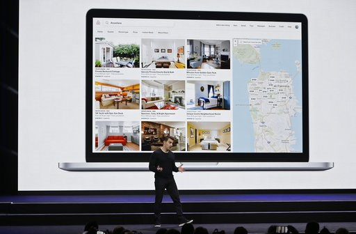 (AP Photo/Eric Risberg, File). FILE - In this Feb. 22, 2018, file photo, Airbnb co-founder and CEO Brian Chesky speaks with San Francisco rental locations projected behind him during an event in San Francisco. A San Francisco couple has agreed to a $2....