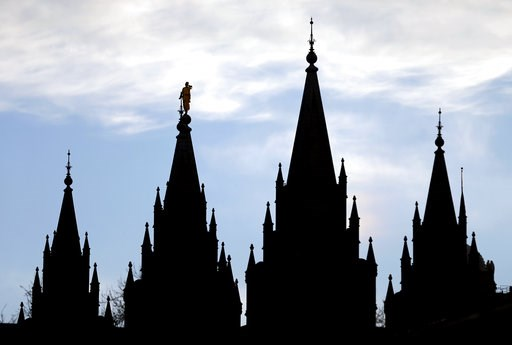 (AP Photo/Rick Bowmer, File). FILE- In this Jan. 3, 2018, file photo, the angel Moroni statue, silhouetted against the sky, sits atop the Salt Lake Temple, at Temple Square in Salt Lake City. After months of fierce debate and campaigning, Mormon church...