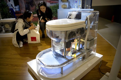 (AP Photo/Mark Schiefelbein). Visitors look at a model of a self-contained toilet at the Reinvented Toilet Expo in Beijing, Tuesday, Nov. 6, 2018. With a jar of human feces on a podium next to him, billionaire philanthropist Bill Gates has kicked off a...