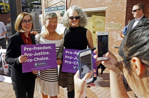 (AP Photo/Don Ryan). FILE - In this Oct. 17, 2018 photo, Gov. Kate Brown, left, poses for photos with supporters after a rally in Portland, Ore. A measure to ban the use of state funds to pay for abortions is on the ballot in Oregon, the state with the...
