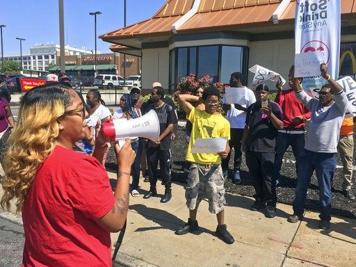 "(AP Photo/Jim Salter). FILE - In this Aug. 24, 2017 file photo, Gennice Mackey uses a bullhorn to lead a chant of ""Save the Raise!"" outside a McDonald's restaurant in St. Louis. Missouri is notable for having three left-leaning proposals on its 2018 ba..."