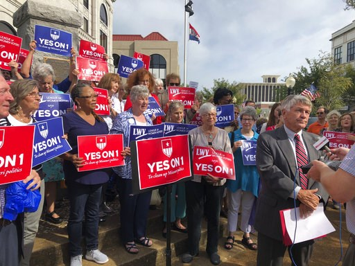 (AP Photo/David A. Lieb, File). FILE - In this Aug. 31, 2018 file photo, supporters of Missouri's redistricting ballot measure hold signs behind former state Sen. Bob Johnson as he serves as their spokesman during a press conference outside the Cole Co...