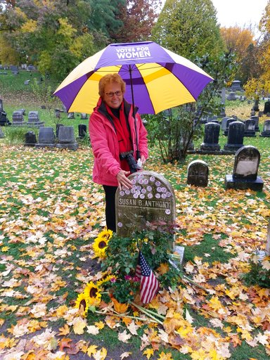 (Deborah L. Hughes/National Susan B. Anthony Museum & House via AP). In this photo provided by the National Susan B. Anthony Museum & House, Emily Jones poses at the grave of Susan B. Anthony in Rochester, N.Y., Tuesday, Nov. 6, 2018. Voters sh...