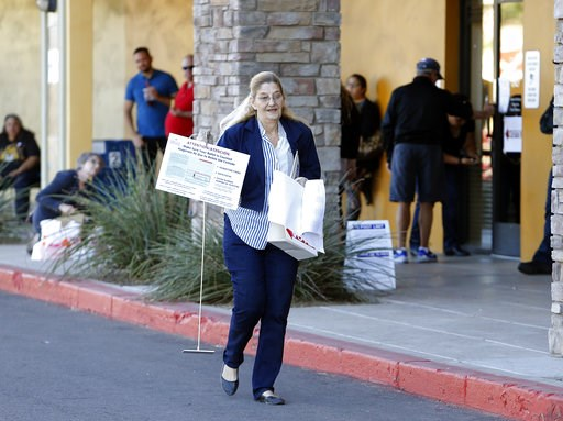 (AP Photo/Rick Scuteri). A volunteer moves supplies to a relocated polling station, Tuesday, Nov. 6, 2018 in Chandler, Ariz. The new polling station opened four hours late after the original location did not open due to the buildings' foreclosure overn...