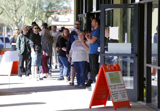 (AP Photo/Rick Scuteri). Voters wait in line to cast their ballots at a relocated polling station, Tuesday, Nov. 6, 2018 in Chandler, Ariz. The new polling station opened four hours late after the original location did not open due to the buildings' fo...