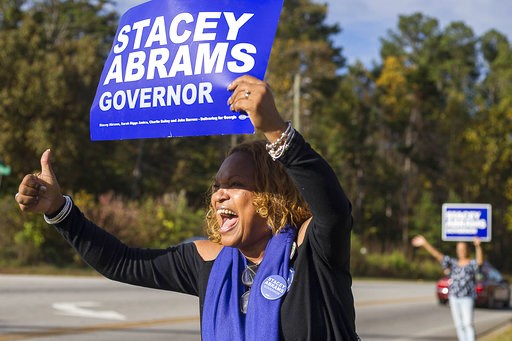 (Alyssa Pointer /Atlanta Journal-Constitution via AP). Activist Jo Handy reacts to drivers as she shows her support for Georgia gubernatorial candidate Stacey Abrams at the Deshon Plaza Shopping Center in Stone Mountain, Tuesday, Nov. 6, 2018.